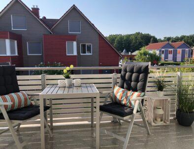 Großer Balkon mit Tisch und Liegestühlen